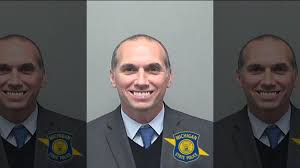 Macomb County Prosecutor Eric Smith facing 22 years for embezzlement, grins  in mug shot