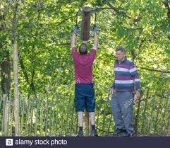 Man Using A Heavy Duty Post Rammer Driver To Force A Thick Wooden Stake Into The Ground In The Construction Of Boundary Fencing For A Wooded Area Stock Photo Alamy