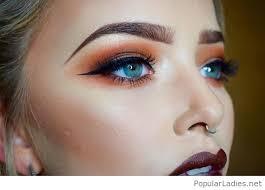 orange and black eye makeup with brown lips