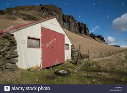 Iceland South Iceland Old Barn With Car Tire Fence Mountains Blue Sky Stock Photo Alamy