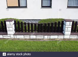 Dark Brown Wooden Picket Fence Mounted On Concrete Foundation Covered With White Stone Tiles In Front Of Suburban Family House Surrounded With Grass Stock Photo Alamy