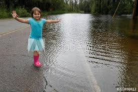 Iva Williamson, 4 years old, plays during a lull in the rains at the edge  of rising flood waters before her evacuation in the aftermath of Hurricane  Florence in Leland, North Carolina -