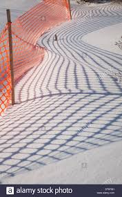 Shadows From An Orange Plastic Snow Fence Make Patterns On The New Stock Photo Alamy