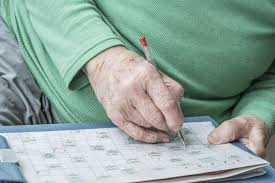 old man solving crossword puzzle stock