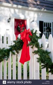 Garland With Red Bow Hanging On White Picket Fence Surrounding Stock Photo Alamy