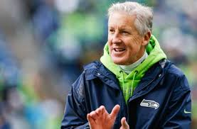 Seattle Seahawks head coach Pete Carroll stands with his players