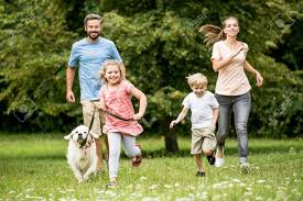 Felices Los Niños Y Los Padres Con El Perro Como Familia Corriendo ...