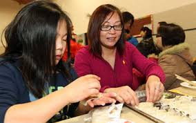 Ten-year-old Sheng Fang and her mother Eileen Lee make dumplings as part of  the