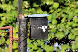 Heavily Used Old Small Black Metal Mailbox With Dilapidated And Cracked Paint Mounted On Partially Rusted