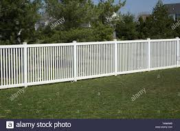 A New White Vinyl Fence By A Grass Area With Trees Behind It Stock Photo Alamy