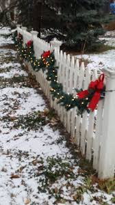 Lighted Garland On The Picket Fence Outdoor Christmas Lights Outdoor Christmas Decorations Christmas Decorations Diy Outdoor