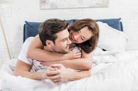 beautiful happy couple hugging in bed