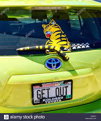 Back Of Yellow Prius With Yellow Tabby Cat Decal Cat Tail Windshield Wiper And Paw Decals With A Vanity License Plate Reading Get Out Stock Photo Alamy