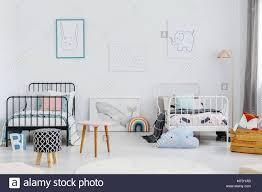Patterned Stool In Spacious Children Bedroom Interior With Posters Above White And Black Bed Real Photo Stock Photo Alamy
