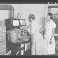 Ada Turner and Evelyn M. Driver home management and home economics  supervisor, canning English peas with pressure cooker in Mrs. Missouri  Thomas' kitchen. Flint River Farms, Georgia - PICRYL Public Domain Image
