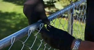 A Person Ties A Chain Link Fence To A Rail Chain Link Fence Fence Landscaping Front Yard Fence