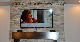 flat screen tv on a stone fireplace