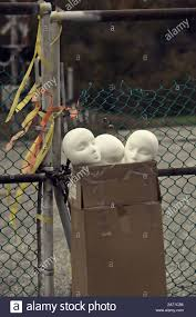 Abandon Mannequin Heads In A Cardboard Box Beside A Chain Link Fence Stock Photo Alamy