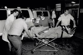 1989 - Ambulance workers, a nurse and a policeman wheel Sofia Cook ...