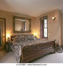 large mirror above sleigh bed in