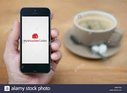 a man looks at his iphone which displays the my voucher codes logo