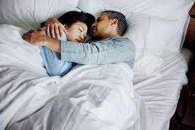 couple hugging on a bed stock photo by