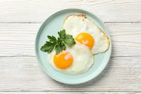 Plato con huevos fritos en mesa de madera, vista superior | Foto Premium
