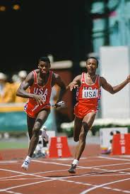 Carl Lewis takes the handoff from Calvin Smith as he begins the ...