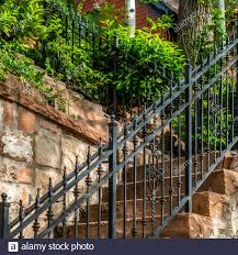 Square Frame Outdoor Staircase With Stone Steps And Black Metal Railing Against A Fence Stock Photo Alamy