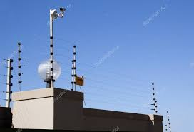 Electric Fence And Security Camera Atop Boundary Wall Stock Photo C Lcswart 44991601