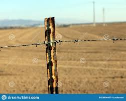 Rusted Barb Wire Fence With A Background Of A Dry Tilled Field Stock Image Image Of Fence Barrier 138596457