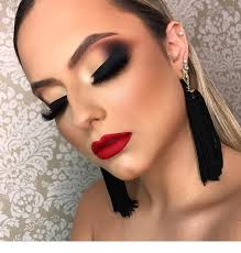 black eye makeup and earrings with red lips