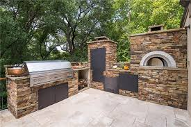 outdoor kitchen with smoker and pizza