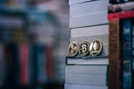 Physical Cryptocurrency Coins are Placed among the Books in a ...