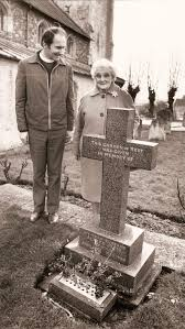 Rev. Julian Thomson with Mrs Addie Mitchell by The Garden of Remembrance in  Orwell Churchyard.   Couples, Mixed, Religious   Orwell