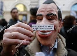 demonstrator wearing Berlusconi mask shows paper reading Editorial ...