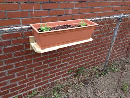 Planter Window Box Hung On Chain Link Fence Shelf Is Made From A Pressure Treated Fencing Plank And Two Metal Hanging Plants Hanging Plants Diy Fence Planters