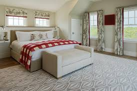 beige bed with red buffalo check throw