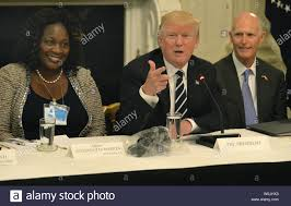 President Donald Trump (C) gestures during remarks as Fontana, California  Mayor Acquanetta Warren (L) and Florida