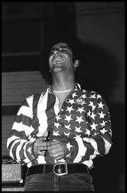 Abbie Hoffman in his American flag shirt, head cocked back, laughing -  Digital Commonwealth