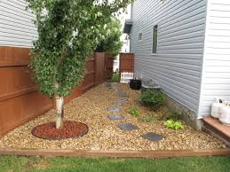 Narrow Side Yard House Design With Brown Gravels And Wooden Fence Trees And Stone Footpath Plus Wooden Shed Landscaping Side Yard Landscaping Gravel Patio Diy