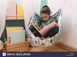 Relaxed Little Girl Reading A Book In Her Hammock Near The Window Funny Lovely Child Having Fun In Her Kids Room Stock Photo Alamy
