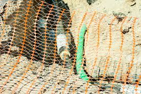 Closeup Of Plastic Orange Safety Net Used As Security Fence On The Street District Heating Pipeline