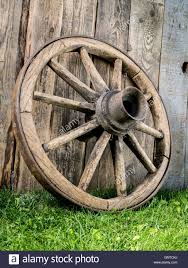 Old Wooden Wagon Wheel Resting Against Rustic Wooden Fence Stock Photo Alamy