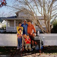 Large Family Standing At Fence In Front Of House Portrait High Res Stock Photo Getty Images