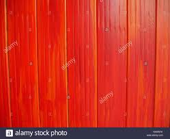 Close Up Of Panels Of Wooden Fence Painted Bright Red But With Orange Stock Photo Alamy
