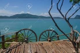 Wooden Terrace With Wagon Wheel Fence Over Blue Sea Stock Photo Picture And Royalty Free Image Image 131610162