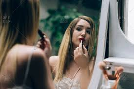 beautiful young woman looking at vine mirror and applying makeup on her face