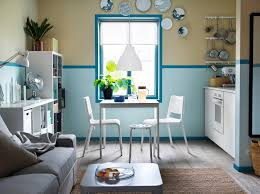 a blue and white kitchen with small vangsta extendable table with two teodores chairs and a