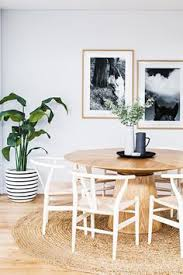 a earthy dining room with framed photography a round woven rug and wishbone chairs